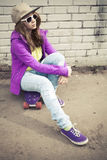 Mädchen in den Jeans und in der Sonnenbrille sitzt auf ihrem Skateboard Stockbild