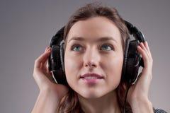 Mädchen in den Kopfhörern stockbild