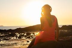 Mädchen in den Kopfhörern hörend Musik in der Stadt bei Sonnenuntergang lizenzfreie stockfotos