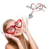 Mädchen in den Kopfhörern und in geformten Gläsern des Herzens Stockfotos