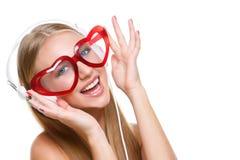 Mädchen in den Kopfhörern und in geformten Gläsern des Herzens Lizenzfreies Stockfoto
