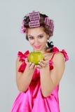 Mädchen in den Lockenwicklern und in einem grünen Apfel in der Hand Apple im Fokus Stockfotos