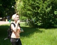 Mädchen in den Parkschlag-Seifenluftblasen. Stockbild