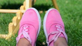 Mädchen in den rosa Mokassinen, die auf grünem Gras im Sommer stillstehen stock footage
