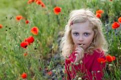 Mädchen in den roten Blumen Stockbilder