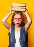 Mädchen in den roten Gläsern mit Büchern Stockfoto