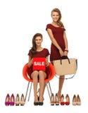 Mädchen in den roten Kleidern mit Schuhen, Tasche und Verkauf unterzeichnen Stockfoto