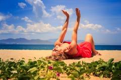 Mädchen in den Rotlügen auf Sand hebt Hände nahe Vordergrundkriechpflanzen an Stockbild