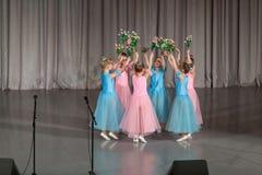 Mädchen in den schönen Kleidern mit Blumen führt durch Lizenzfreie Stockbilder