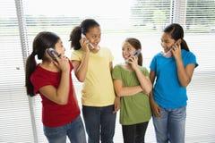 Mädchen an den Telefonen. Lizenzfreies Stockbild