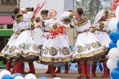 Mädchen in den traditionellen Kostümen, die auf Stadium tanzen Stockbilder