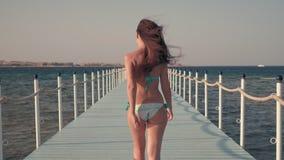Mädchen in der Badebekleidung gehend auf den Pier, während Wind durchbrennt stock footage