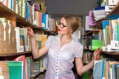 MÄDCHEN IN DER BIBLIOTHEK ZWISCHEN Gestellen mit Büchern, eine schöne Blondine Lizenzfreie Stockbilder