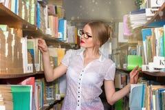 MÄDCHEN IN DER BIBLIOTHEK ZWISCHEN Gestellen mit Büchern, eine schöne Blondine Lizenzfreie Stockfotografie