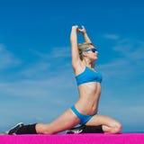 Mädchen in der blauen Sportkleidung und in der Sonnenbrille ausbildend auf Freilicht Lizenzfreie Stockbilder