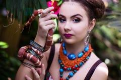Mädchen in der ethnischen Kleidung im tropischen Garten mit Schlange Stockbilder