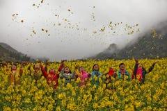 Mädchen der ethnischen Minderheit auf einem Gebiet von Canola lizenzfreie stockfotos