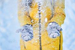 Mädchen in der gelben Jacke wirft Schnee in der Luft im kühlen Wetter lizenzfreie stockfotografie