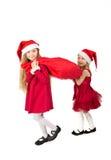 Mädchen in der Glocke Santa Claus, die eine Tasche von Geschenken schleppt Lizenzfreie Stockfotos