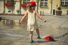Mädchen in der heißen Sommerstadt mit Wasserberieselungsanlage Stockbild