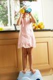 Mädchen in der Küche, die bei oben sich waschen hilft Stockfotografie