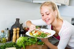 Mädchen an der Küche, die Salat zubereitet Stockfoto