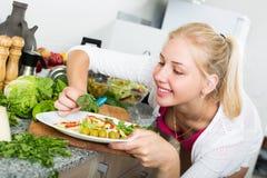 Mädchen an der Küche, die Salat zubereitet Lizenzfreies Stockbild