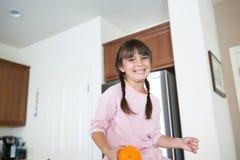 Mädchen in der Küche mit einem großen Lächeln, das eine Orange hält lizenzfreie stockfotografie