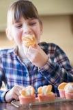 Mädchen in der Küche nach Hause gemachte Schalen-Kuchen essend Stockbild