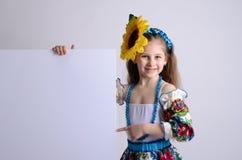 Mädchen in der nationalen ukrainischen Klage mit einer Sonnenblume auf ihrem Kopf Stockbilder