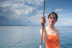 Mädchen in der Orange und im Meer Stockbild