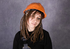 Mädchen in der orange Weste des Schutzhelms, die Hammerwerkzeug hält lizenzfreie stockfotos