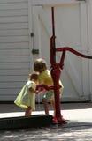Mädchen an der Pumpe Stockfoto
