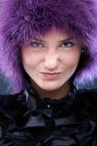 Mädchen in der purpurroten Perücke, die Gesicht zieht Stockfotografie
