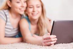 Mädchen an der Pyjamapartei unter Verwendung der Tablette Lizenzfreies Stockbild
