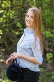 Mädchen in der Reitkleidung und Sturzhelm auf einem hellen Hintergrund, das Konzept des Jockeys stockfoto