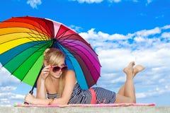 Mädchen in der Retro- Art durch Farbenregenschirm auf dem Strand Stockbild