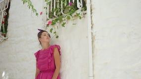 Mädchen in der rosa kurzen Kleiderstellung an der weißen Steinwand an einem Sommertag stock footage