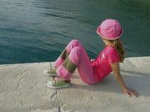 Mädchen in der rosafarbenen Schutzkappe und im blauen Meer Stockbilder