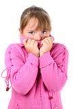 Mädchen in der rosafarbenen Strickjacke, die kalt sich fühlt, Selbst umfassend Stockfoto