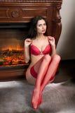 Mädchen in der roten Unterwäsche sitzt nahe Kamin lizenzfreies stockbild