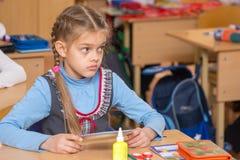 Mädchen in der Schule, zum der Klasse zu bearbeiten hat die Aufgabe und mit einem verwirrten schauenden nicht Lehrer verstanden Lizenzfreie Stockfotografie