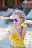 Mädchen in der Sonnenbrille auf dem Strand trinkend von einem Rohr des Mangosafts Lizenzfreies Stockbild