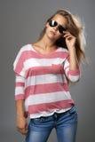 Mädchen in der Sonnenbrille auf grauem Hintergrund Stockfotos