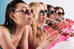Mädchen in der Sonnenbrille Cocktails beim Ein Sonnenbad nehmen trinkend auf schwimmender Matratze Stockfotografie