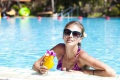 Mädchen in der Sonnenbrille mit Saft im Luxuspool Lizenzfreies Stockfoto