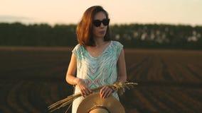 Mädchen in der Sonnenbrille steht auf einem Gebiet am Sonnenuntergang und am Halten von von goldenen Weizenspitzen und -strohhut  stock video footage