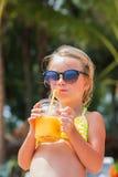 Mädchen in der Sonnenbrille und im Badeanzug ein Glas Mangosaft durch das Meer, auf dem Strand trinkend Stockfotos