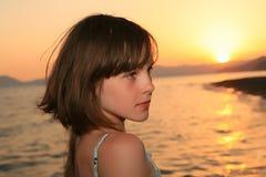 Mädchen an der Sonnenuntergangleuchte Stockfoto