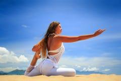 Mädchen in der Spitze in der Yoga asana Lotosrechten hand vorwärts auf Strand Lizenzfreie Stockfotos